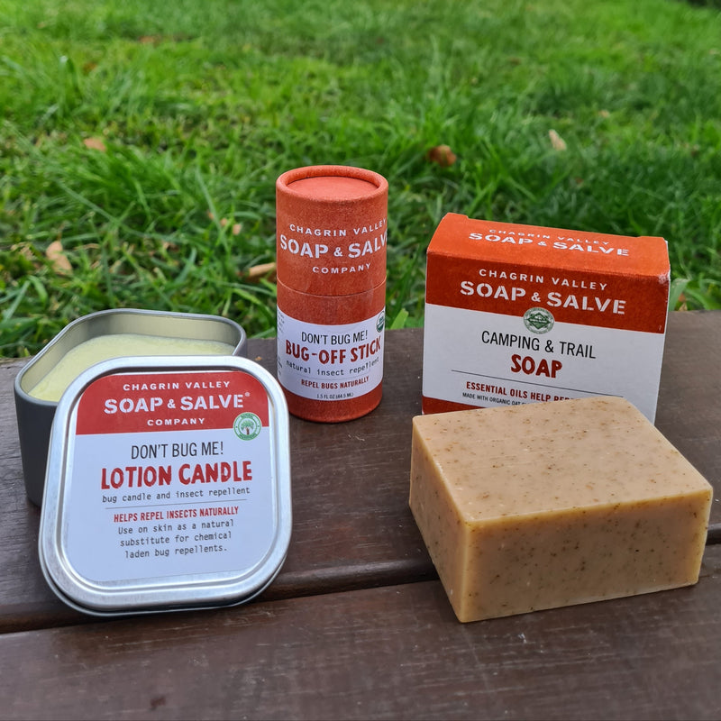 A certified organic and plastic free outdoor gift set including a bug repellent lotion bar stick, a camping soap bar and a bug repellent lotion candle.