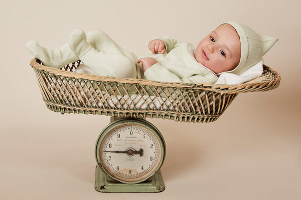Newborn in Green Outfit in Basket