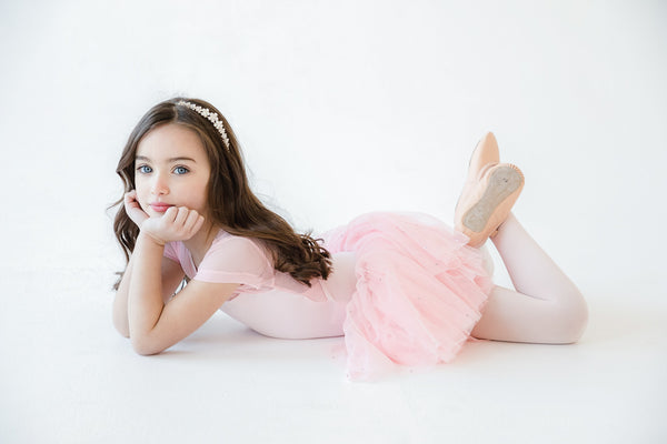 Little ballerina lying on the floor in a tutu with leather ballet shoes on