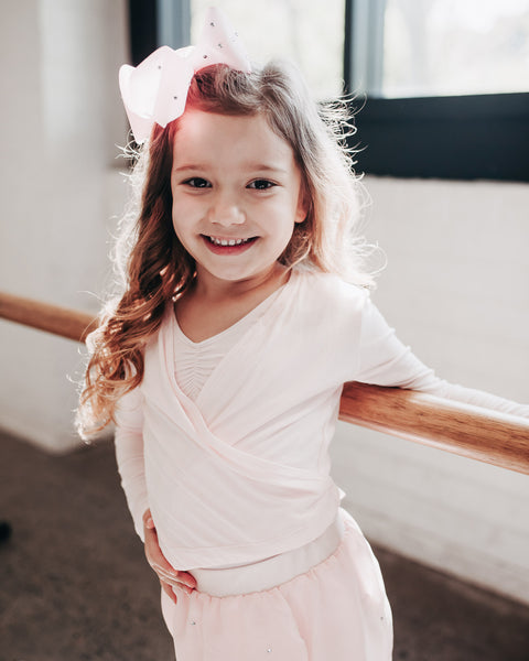 Little Ballerina at the Ballet Barre in Pink Crossover with Bow