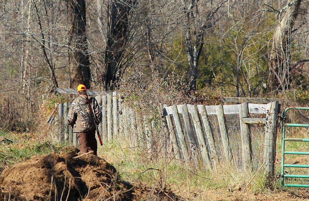 Man walking along a fence while deer hunting.