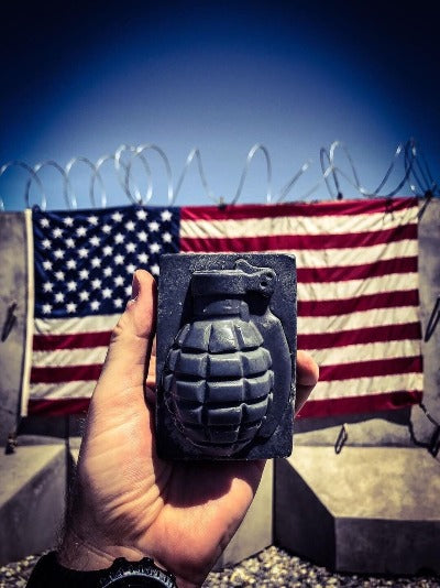 Hand holding grenade soap in front of American flag