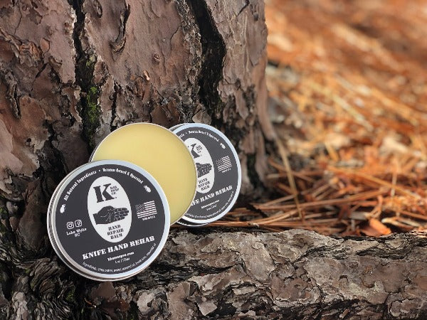 Hand Repair Balm tin open leaning against a tree