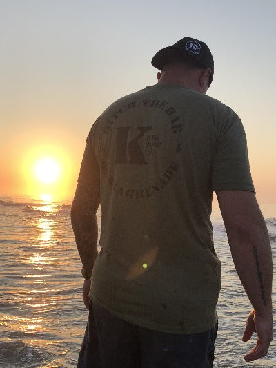 Man with OD Green Triblend K Bar logo shirt at sunset