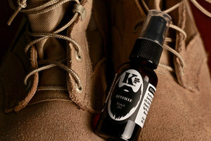 Reveille Beard Oil on top of military boots