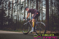 This is an image of a cyclist wearing REA TAPE Premium Lime 5cm x 5mtr Kinesiology Tape - Extra Strong! ACG Massage UK Stockist.