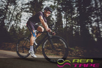 This is an image of a cyclist wearing REA Tape Kinesiology Tape Argyle 5cm x 5mtr Pediatric Tape