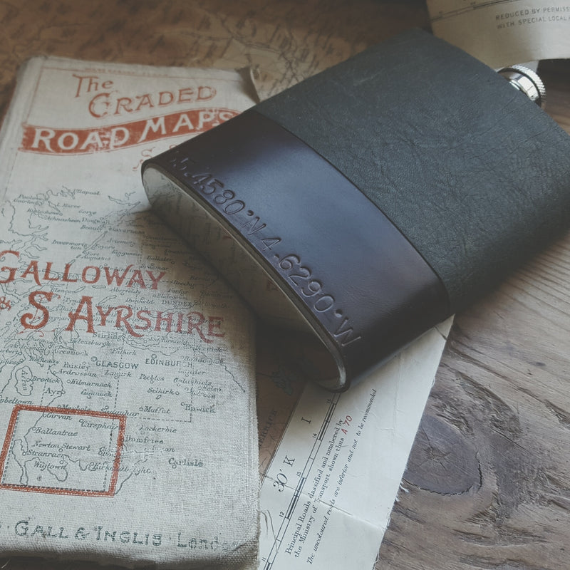 a green and brown leather hip flask with leather stamping on the bottom of the flask, the leather stamping are co-ordinates of a memorable location and can be personalised to you. The flask is positioned on a pile of old antique road maps.