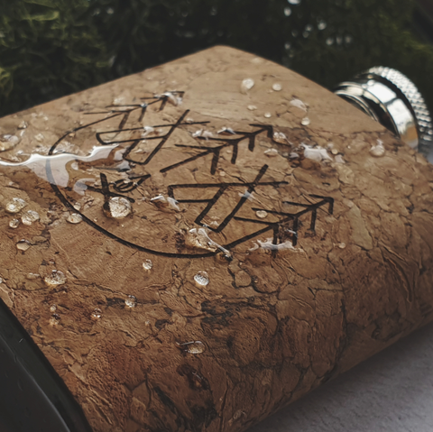 A Cork Wrapped Hip Flask engraved with a campsite image. Water droplets sit on the surface demonstrating its water resistant capabilities. Hip Flask by Hord.