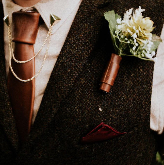Waistcoat decorated with wedding boutonniere with leather wrap and a leather tie