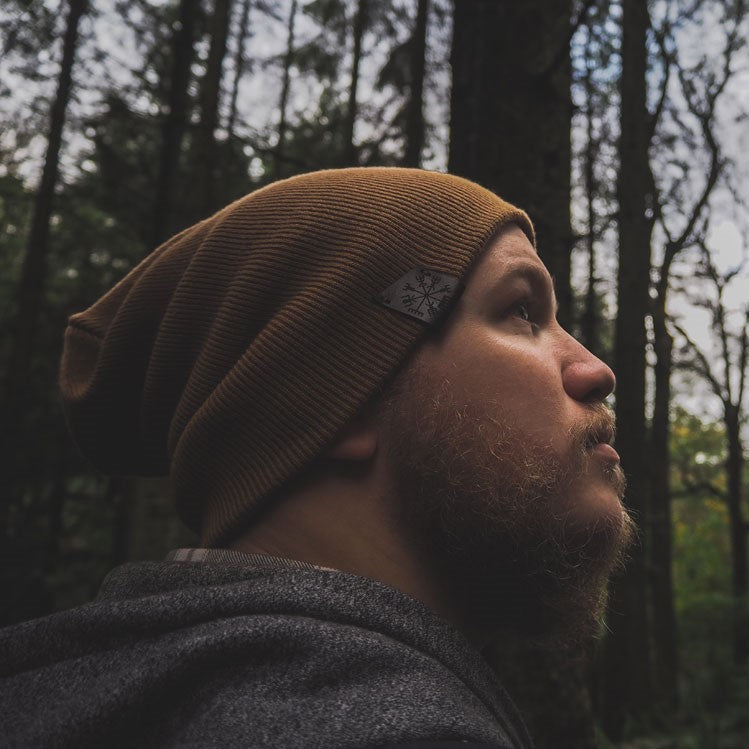 A mustard beanie hat with stitched vegivisir leather patch on dark brown leather. Wooded scenery with bearded man wearing the hat in a slouchy style.
