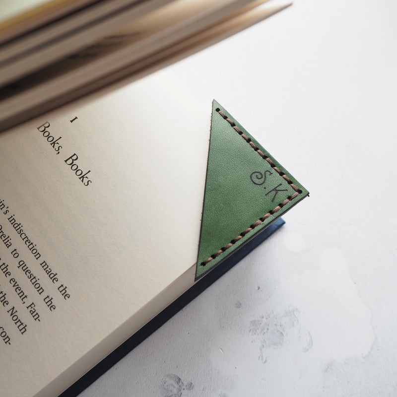 The Corner Bookmark by Hord, a leather bookmark that sits on the corner of your page, dyed in the colour of your choice and engraved in your choice of initials.