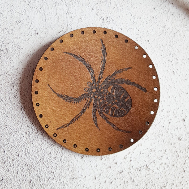 A close up photo of the HORD Spider patch from the entomology collection. A circular patch in dark brown leather with black engraving.
