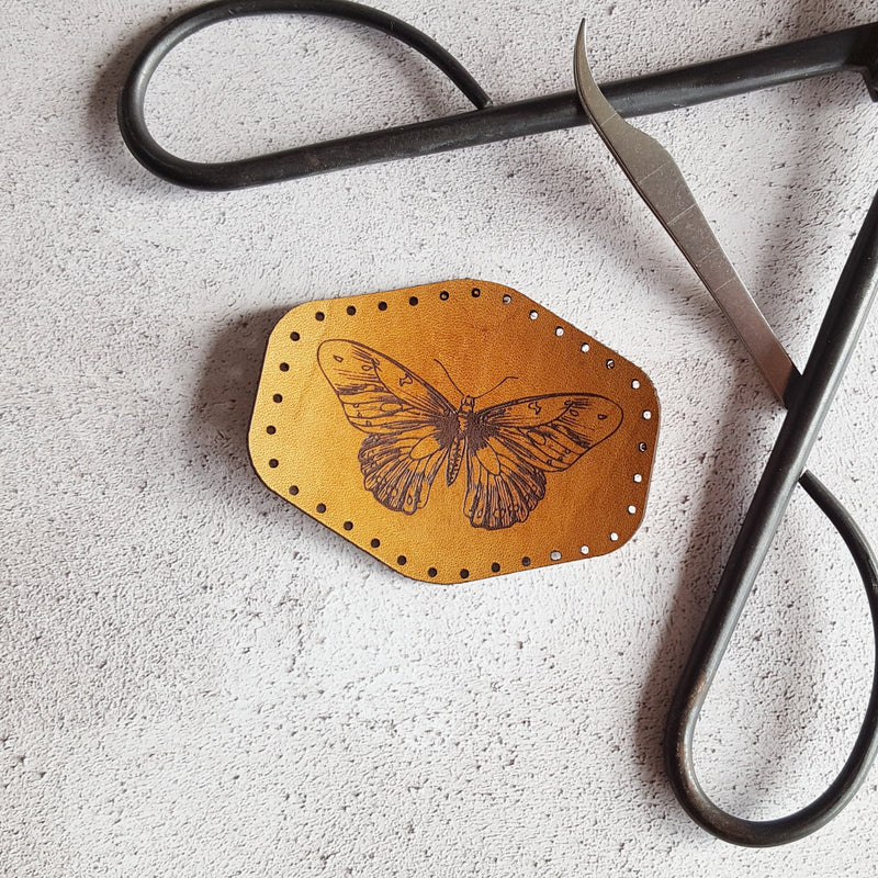 This hand dyed tan leather patch is engraved with an illustrative butterfly and has pre-cut stitch holes to make sewing easy