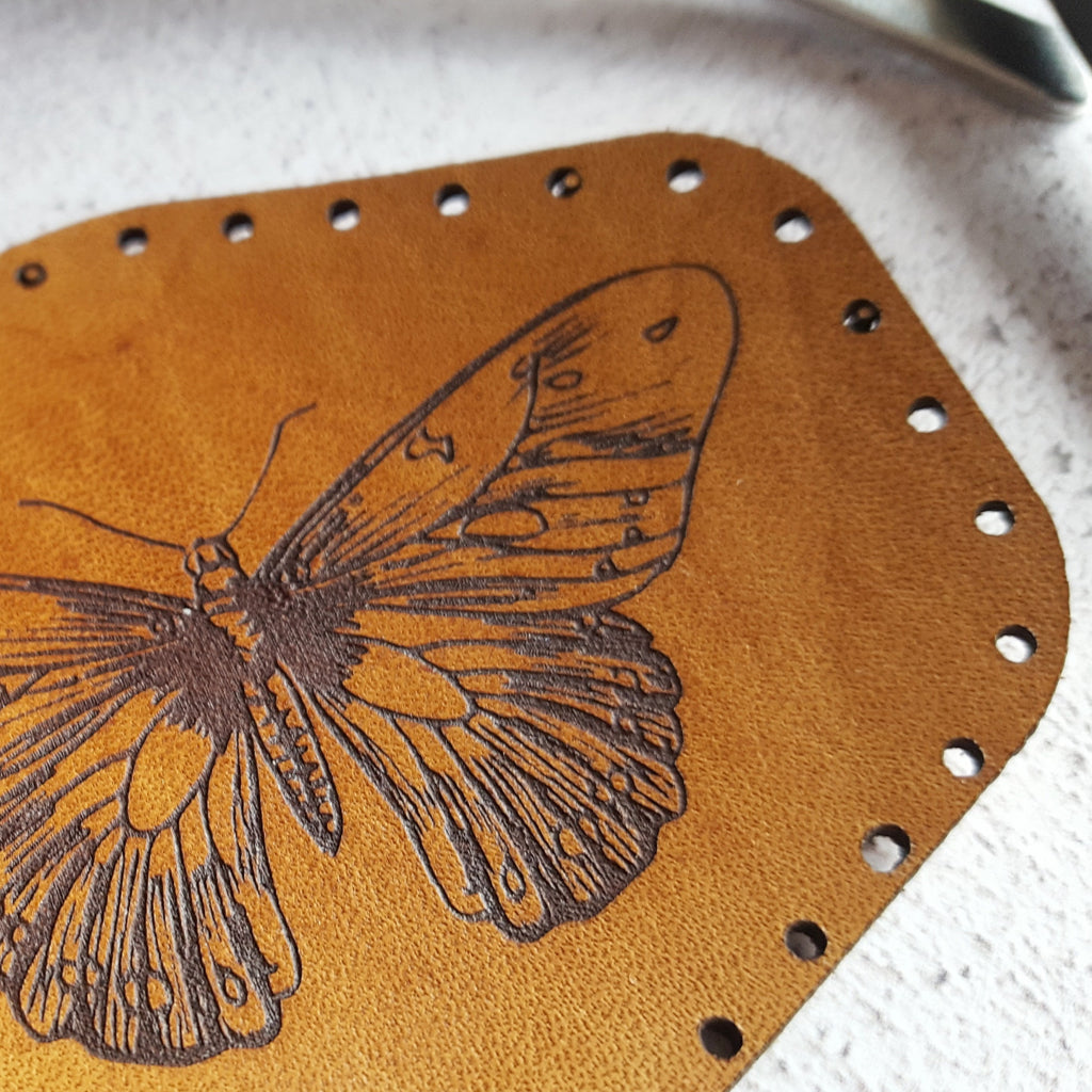 a close up of HORDs tan orange butterfly patch, showing the texture of the grain of the leather and the texture of the black surface engraving