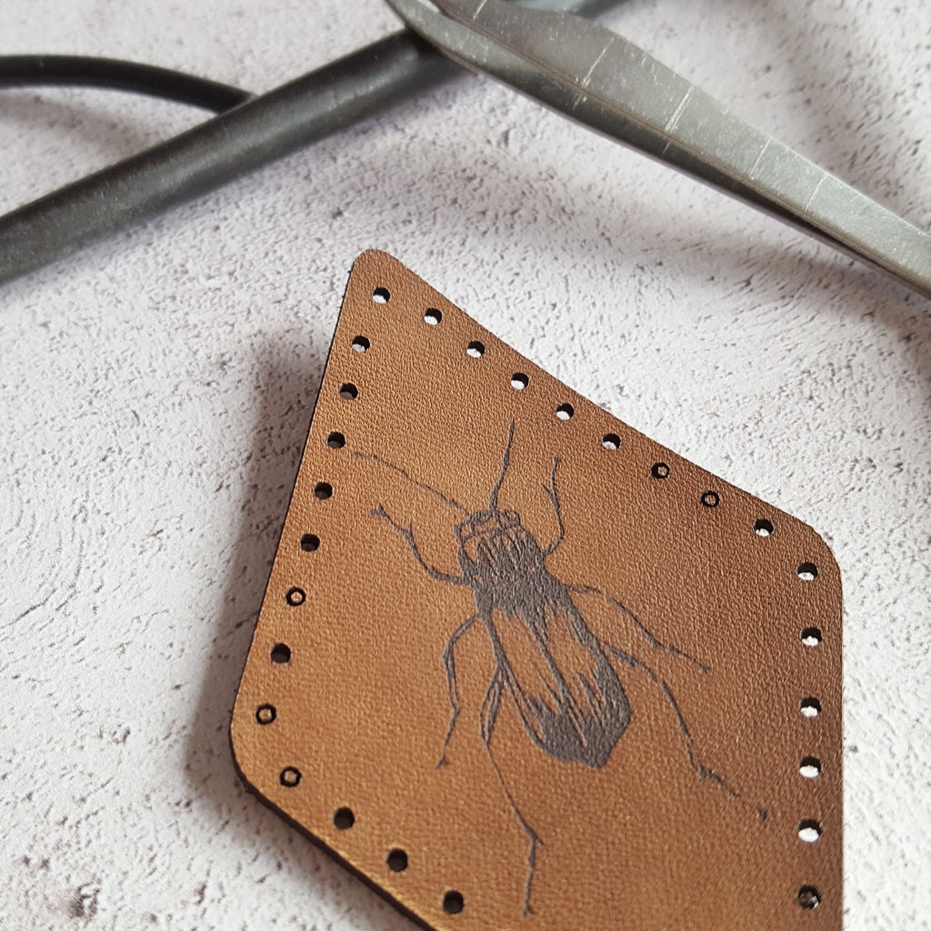 a close up of HORDs beetle patch, showing the texture of the grain of the leather and the depth of the black surface engraving