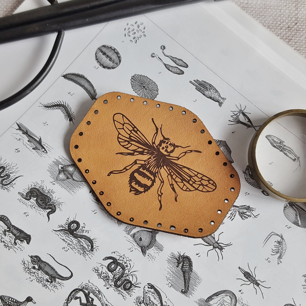 This rounded hexagonal leather patch is hand dyed in a tan colour and engraved with the illustration of a bee - a great gift for those who appreciate bees and everything they do for us, or insects in general