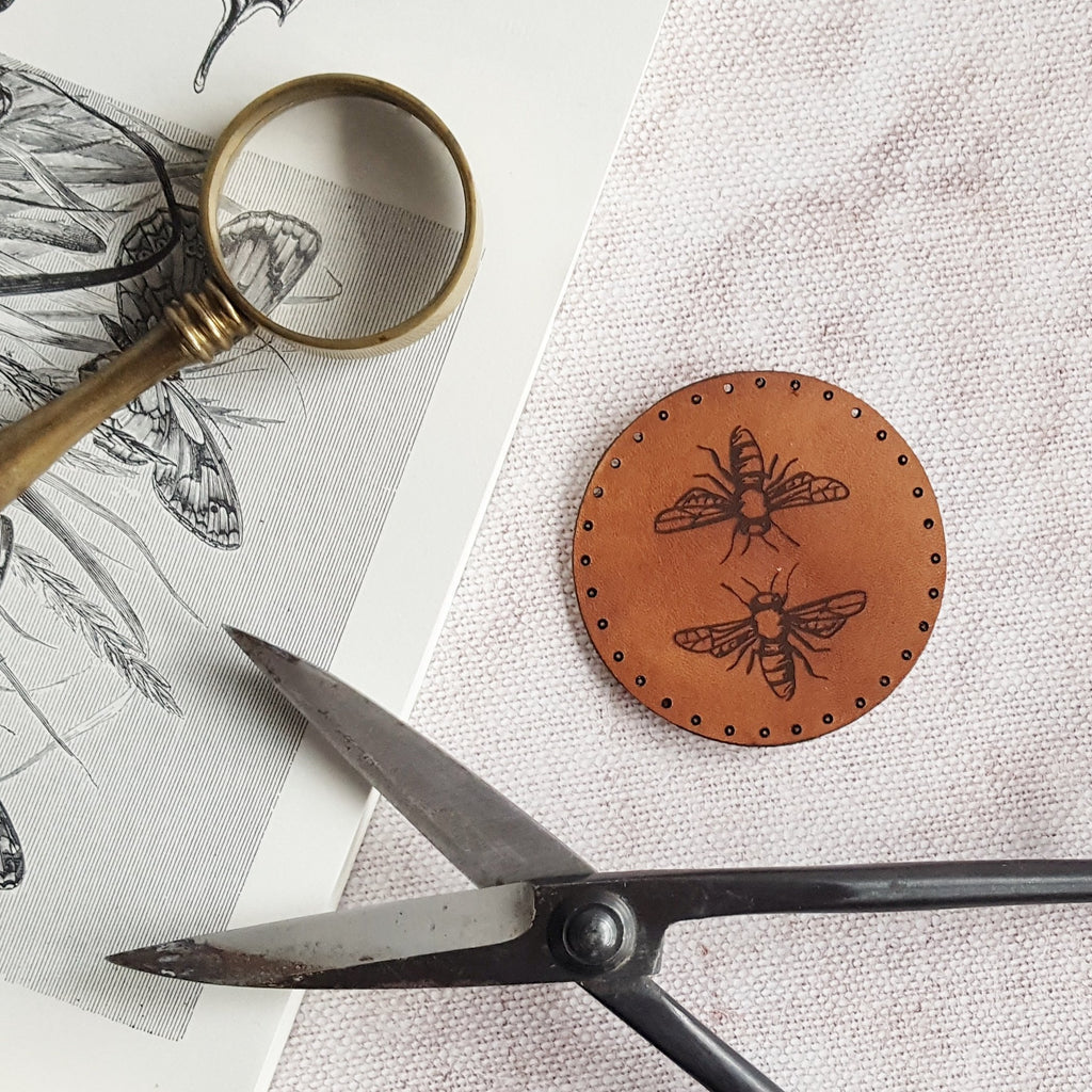 An illustration of two honey bees is engraved on this circular brown leather patch