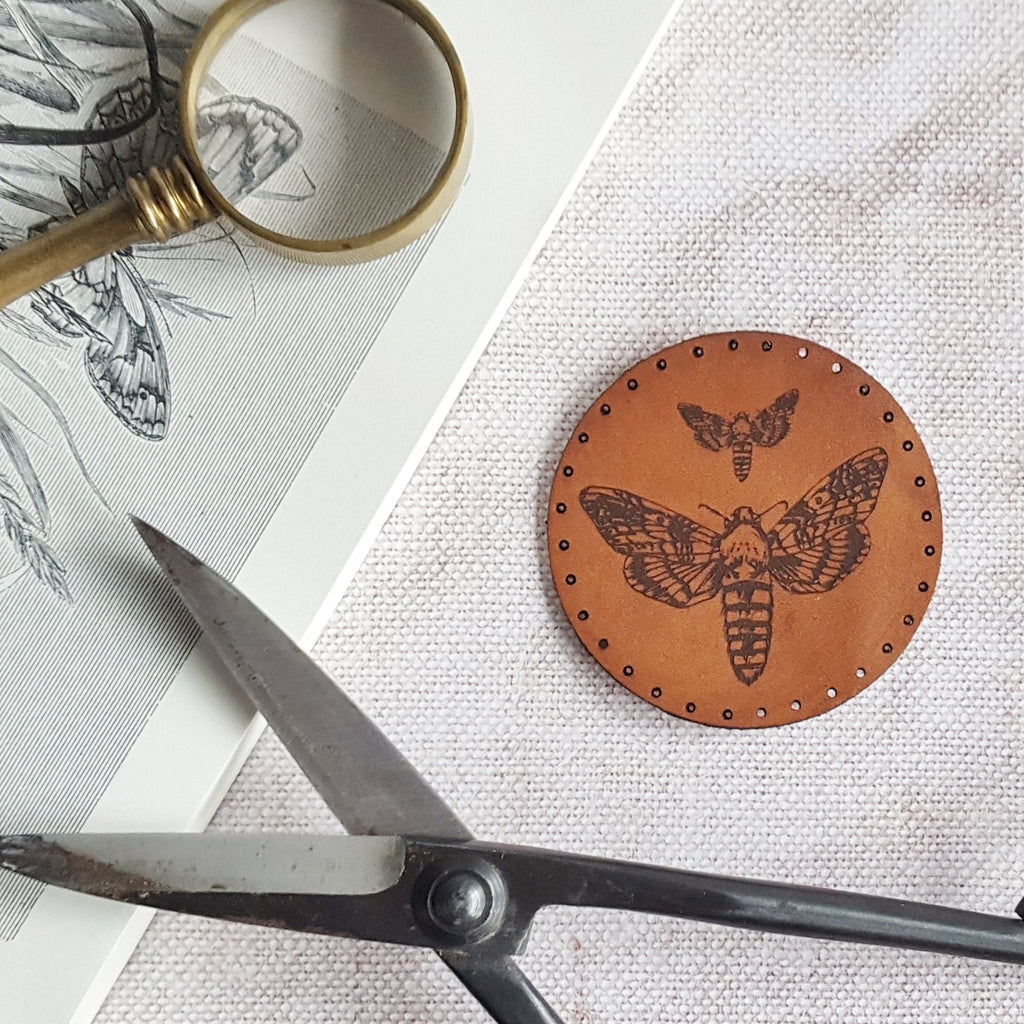 This circular leather patch is hand dyed in a medium brown and engraved with a large and small moth. Pre-cut stitch holes make it easy to sew on.