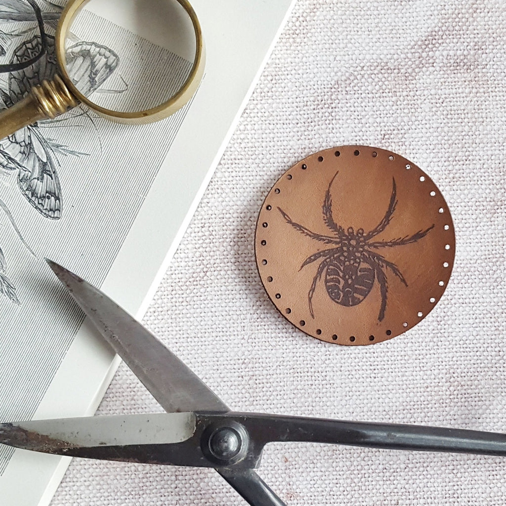 This circular leather patch is hand dyed in dark brown and engraved with a spider. This friendly little arachnid comes with stitch holes ready to easily sew onto your things.