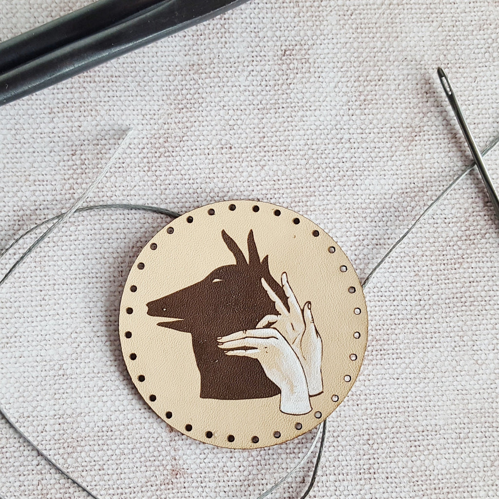 The Wolf Shadow Puppet Patch by HORD - The Wolf Shadow Puppet Patch is made from leather and painted by hand. This leather is veg tan which means that over time, this patch will gain a lovely patina. With pre-cut holes for stitching, this patch can be neatly sewn to your satchel, beanie, hoodie and more.