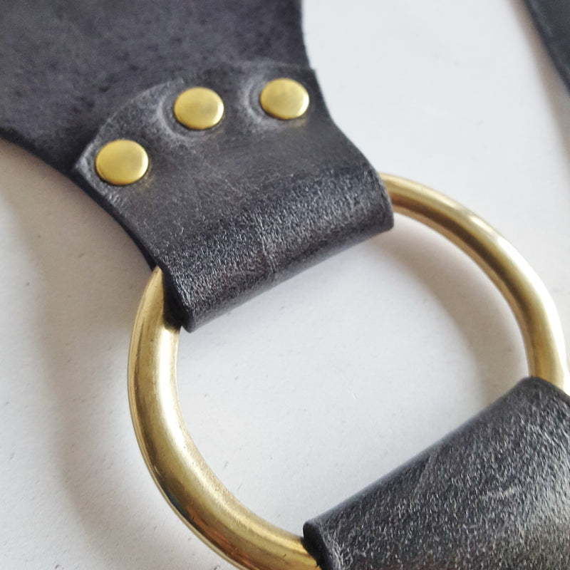 The Hel Harness, comprised of black soft genuine leather and brass rings and rivets. With a cinching wide belt and wishbone shaped straps, by Hord.