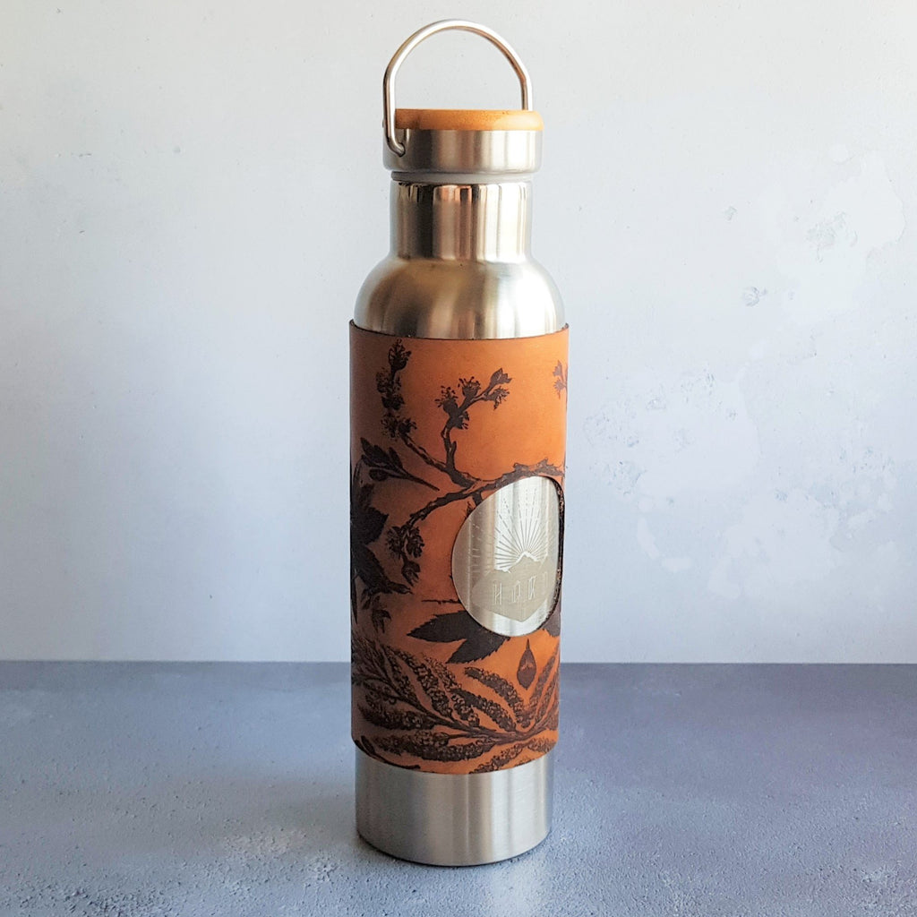 The Botanical Adventure bottle by HORd is engraved with a beautiful botanical pattern. Our double walled water bottles are perfect for outdoor adventurers. Made from insulated double walled stainless steel, with bamboo topped lid that can be hooked on to your rucksack. The hand dyed leather wrap is removable for easy cleaning and the bamboo lid can be engraved with your choice of initials.