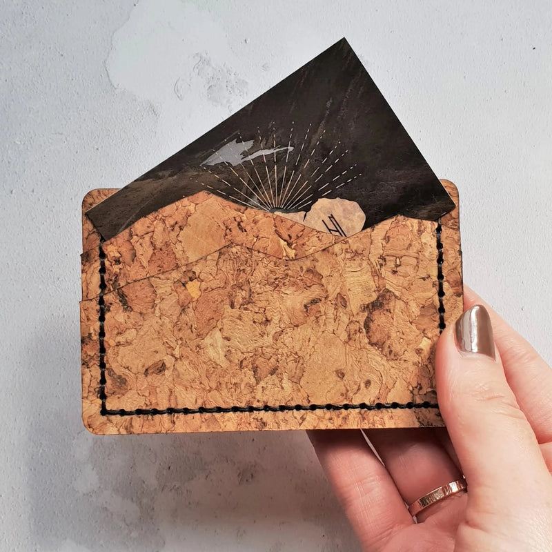 the natural cork mountain shaped credit and debit card holder held in hand to demonstrate the handy size