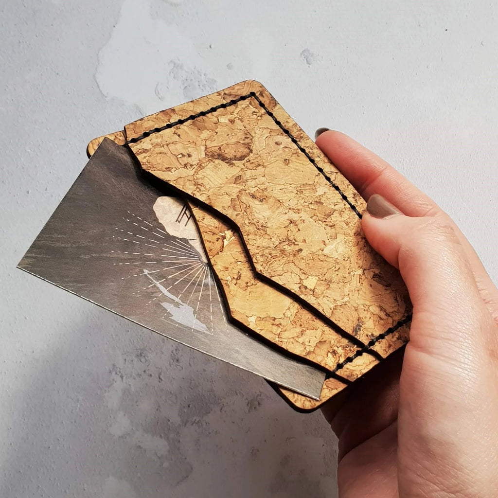mountain shaped wallet and card holder made with textural and resilient natural flecked cork in a pale tan colour with black hand stitching