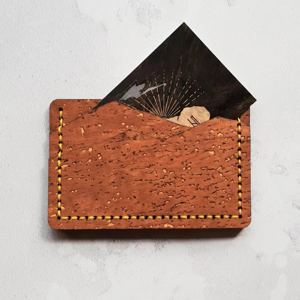 The slimline cork mountain card wallet hand sewn with bright yellow waxed linen thread and perfect for men and women who love adventuring outside