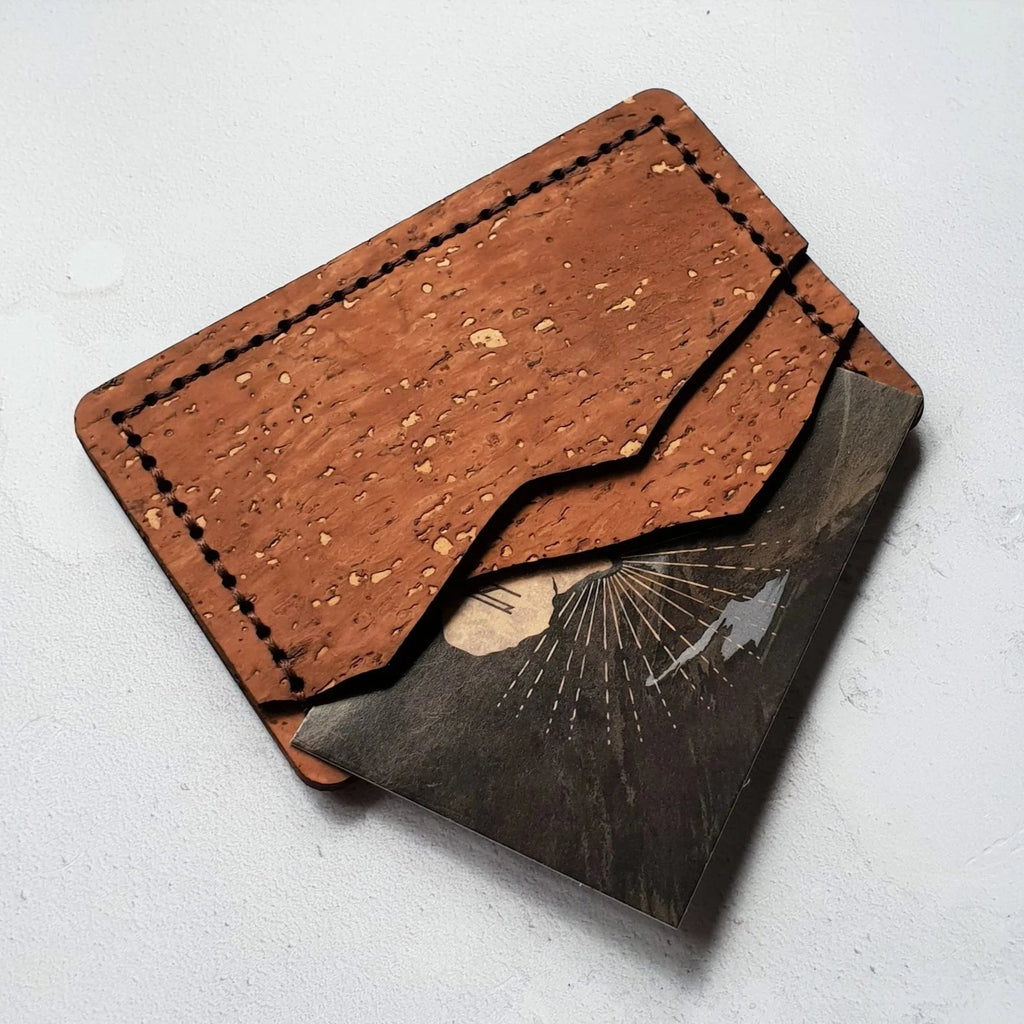 mountain shaped credit card holder made from resilient brown cork with a dimpled texture, hand stitched in dark brown thread