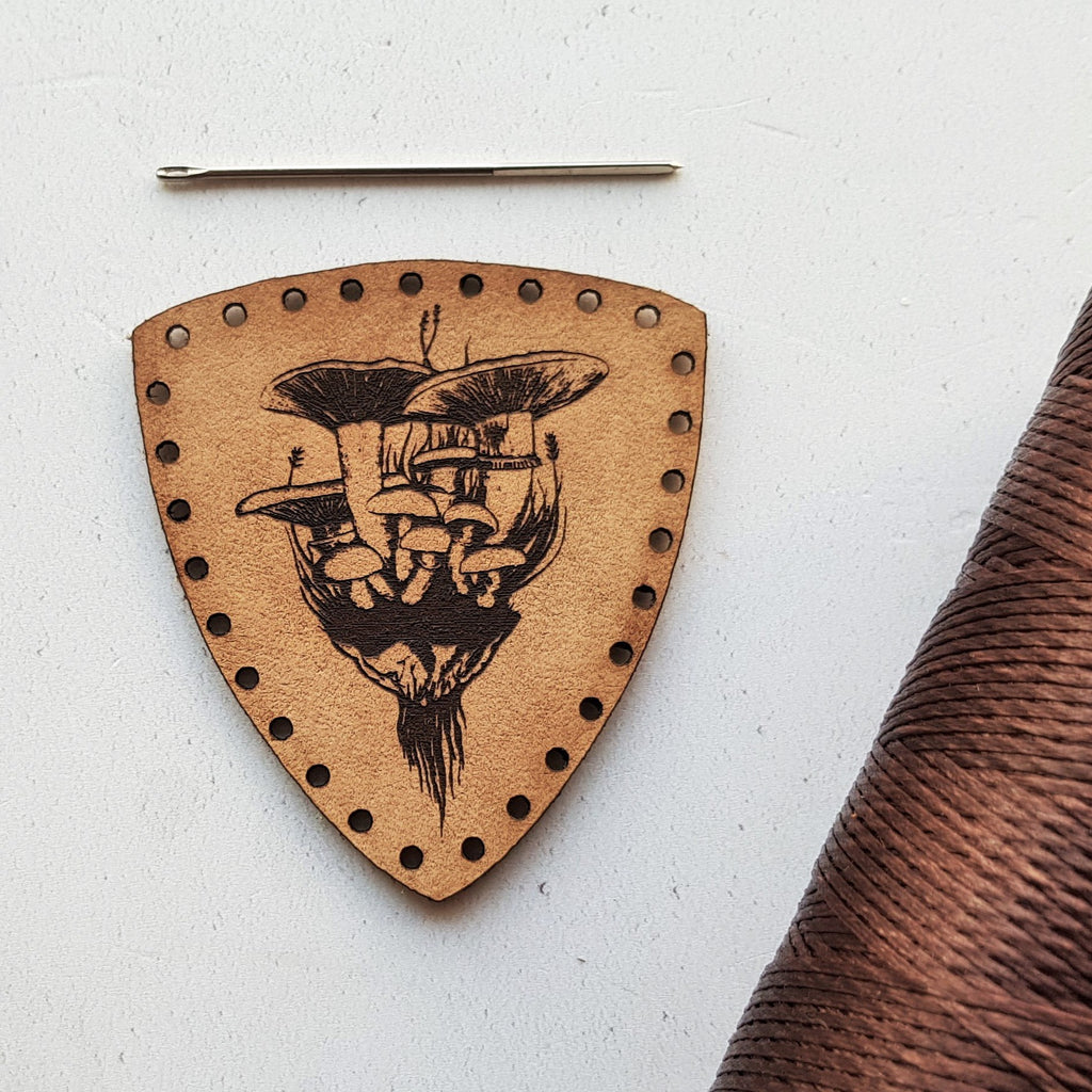 This shield shaped leather patch is engraved with a bunch of wild fungus pulled from the earth on a foraging expedition. Pre-cut patch holes make this easy to stitch onto your foraging bag.
