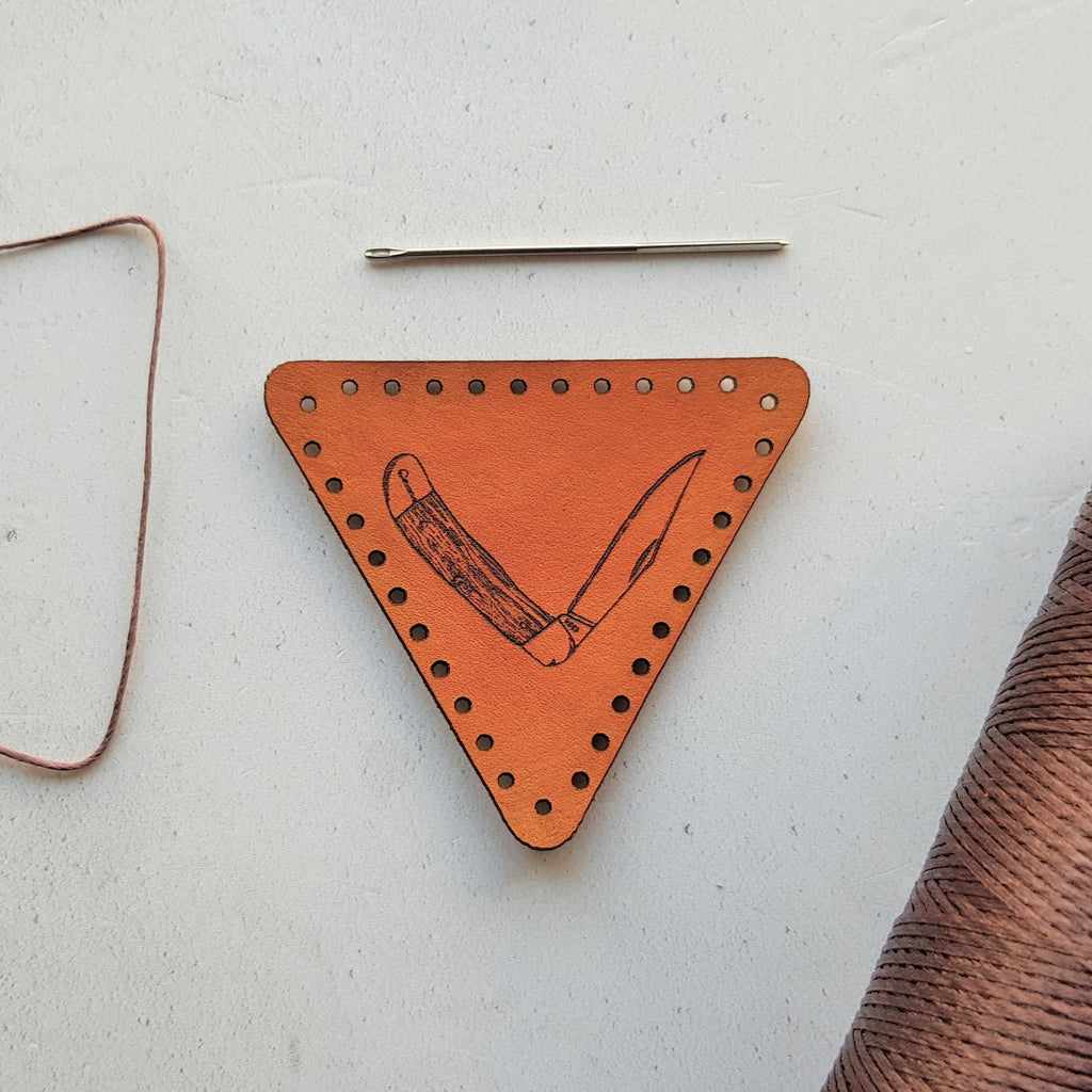 The survivalist leather patch by hord is an orange-tan trangular leather patch engraved with a partly folder Opinel style survival knife