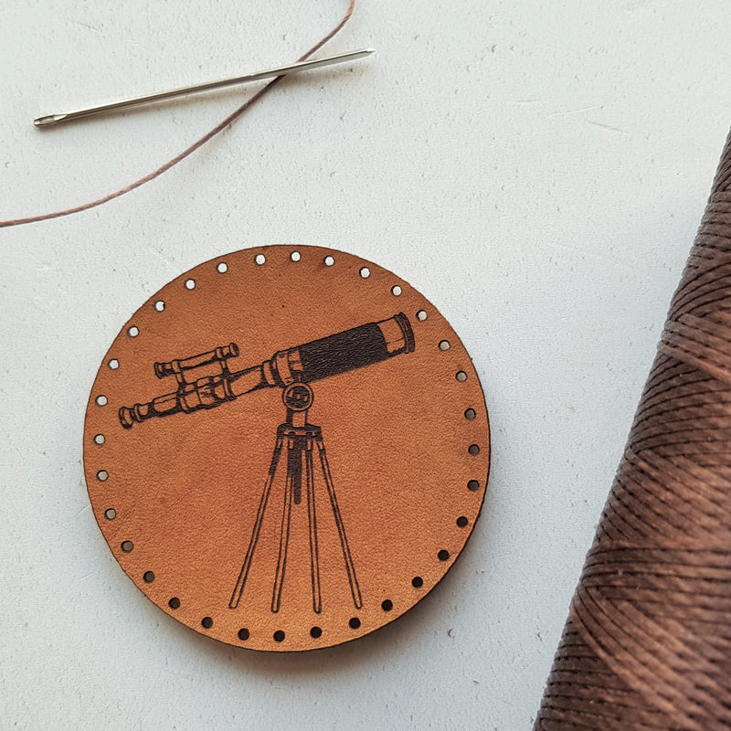 A circular leather patch hand dyed in light brown dye and engraved with a vintage style telescope, perfect for men, women and children who love to gaze at the stars and beyond.