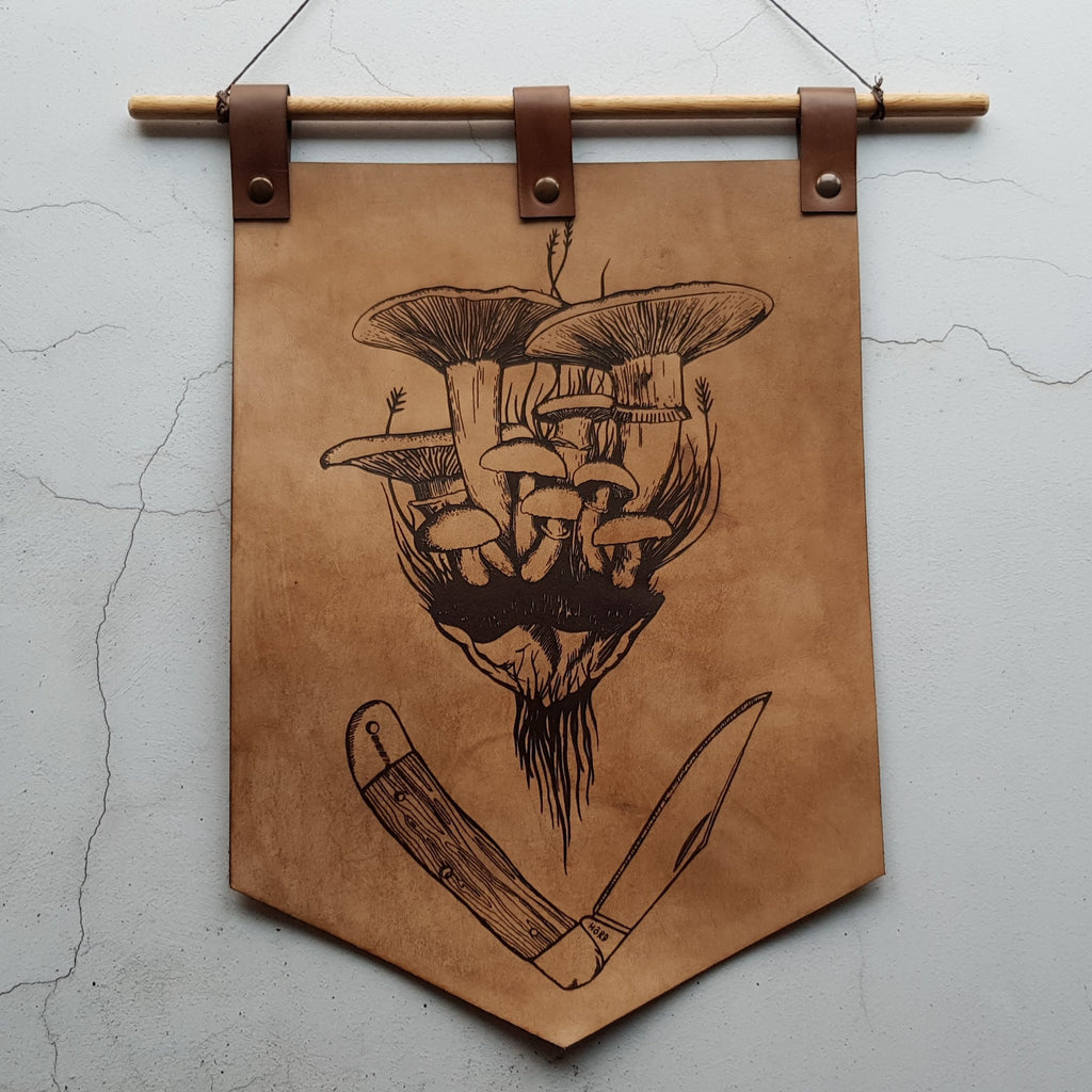 The Forager Banner by HORD is adorned with illustrations of a cluster of wild mushrooms and a survival knife. A great accessory to decorate your walls.