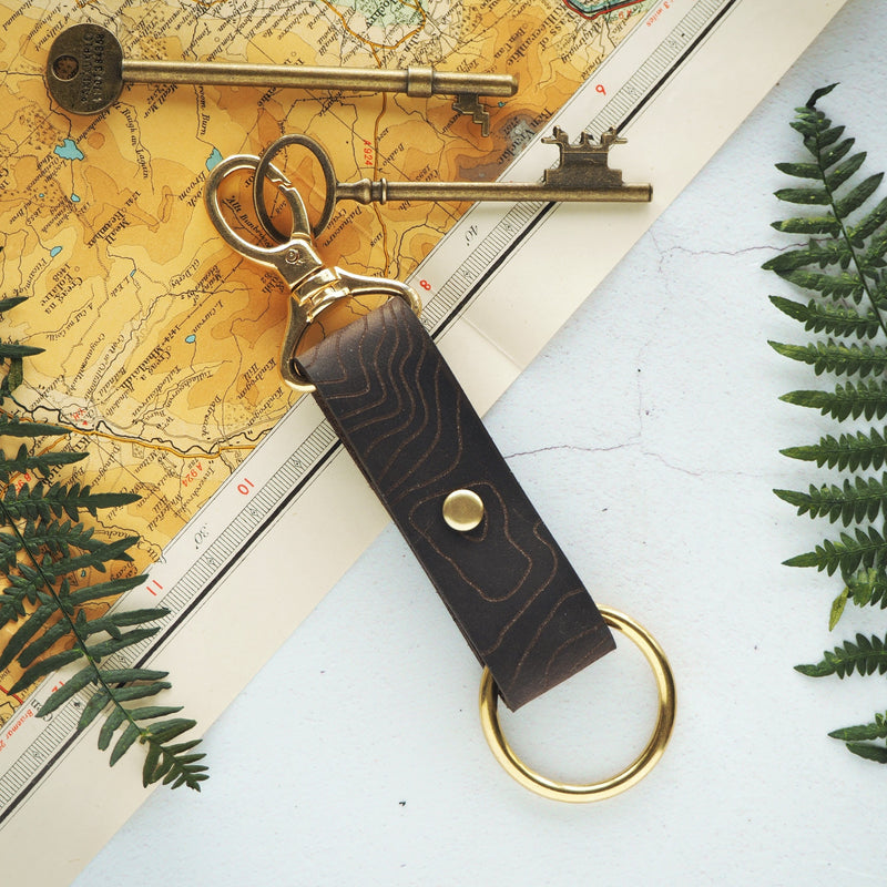 The Custom Topography Key Fob by Hord - Your colour choice of sturdy genuine leather is riveted together to hold a swivel clip and O-ring. This metal hardware provides a multitude of practical uses, from holding keys, to clipping it on your belt or belt loop. Pictured is the Soft Brown Leather and Brass hardware.