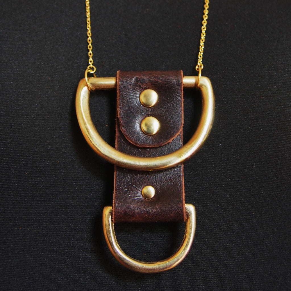 The Wane Necklace is inspired by the phases of the moon. Soft brown leather is riveted around two solid brass d-rings, chunky and rugged. By Hord.