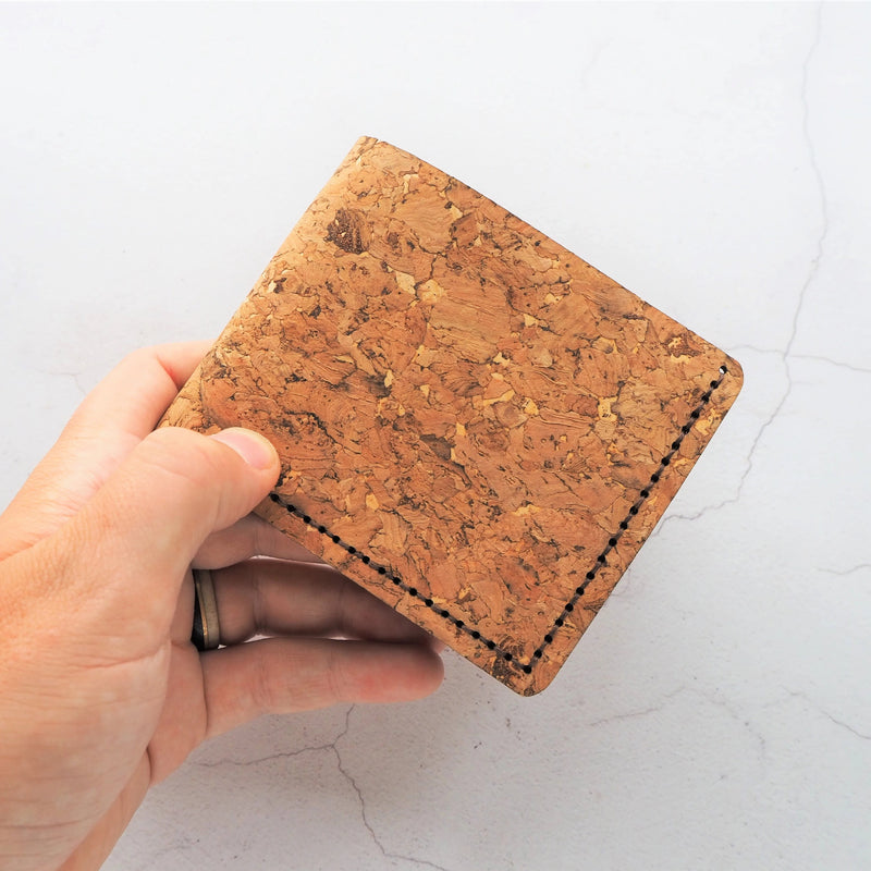 Our full size cork wallet, folded in half to show the size in hand. Beautiful textural flecked natural cork and dark brown stitching makes this a luxurious and sturdy present