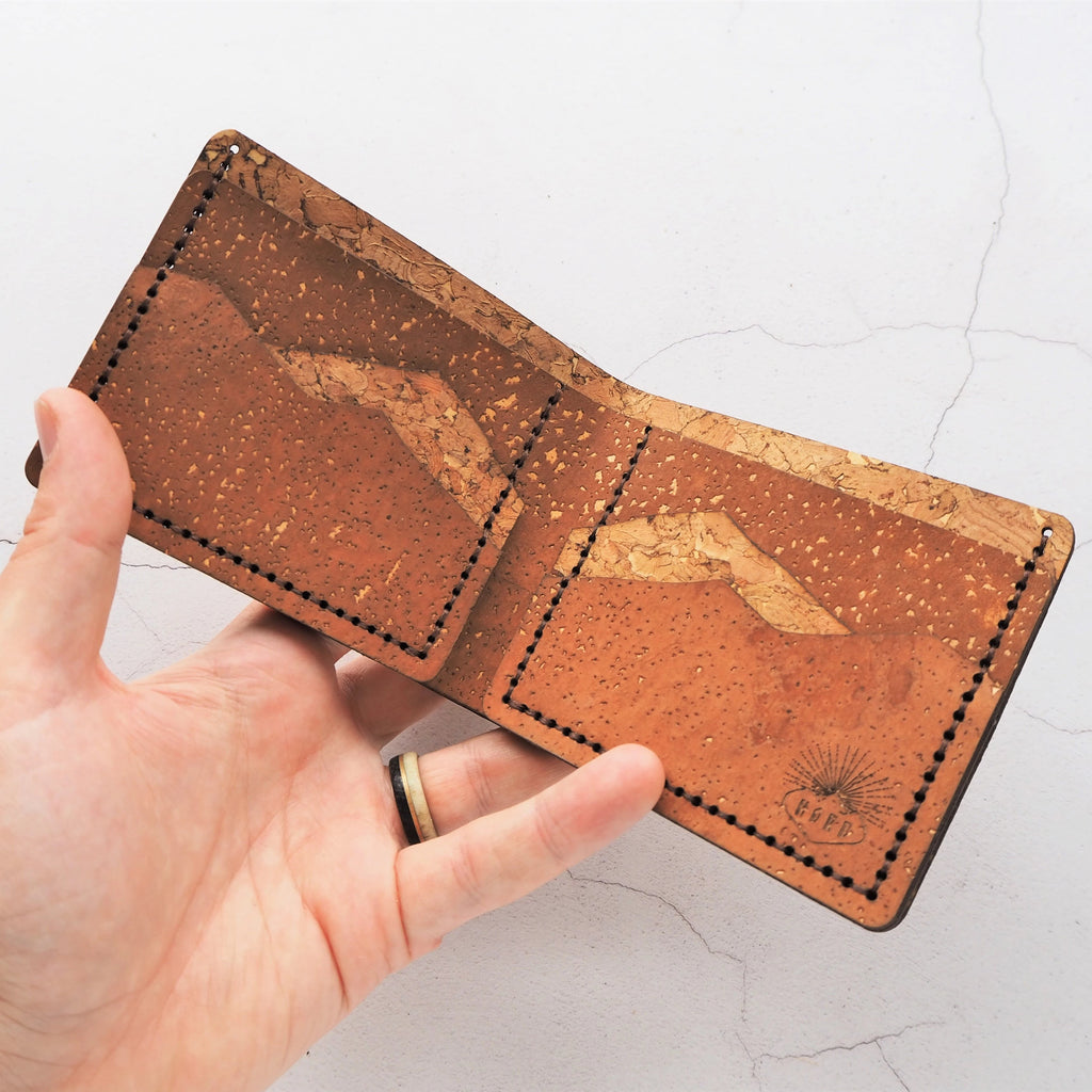 Full size bi-fold wallet with mountain card slots in a mixture of light brown and tan natural cork colours. A very textural and tactile item which makes a perfect gift.