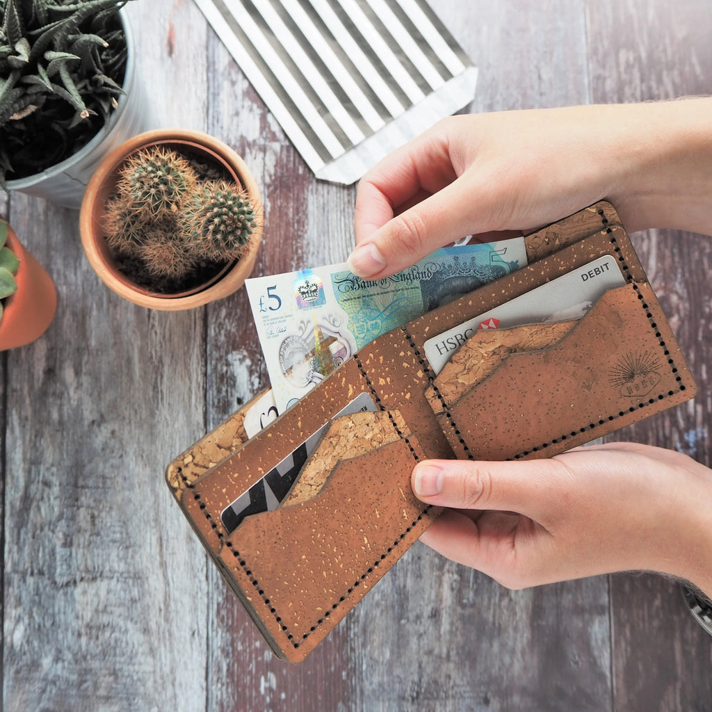 Full size bi-fold wallet with mountain card slots in a mixture of light brown and tan natural cork colours. In use at a shop, purchasing plants for the home with this stylish wallet