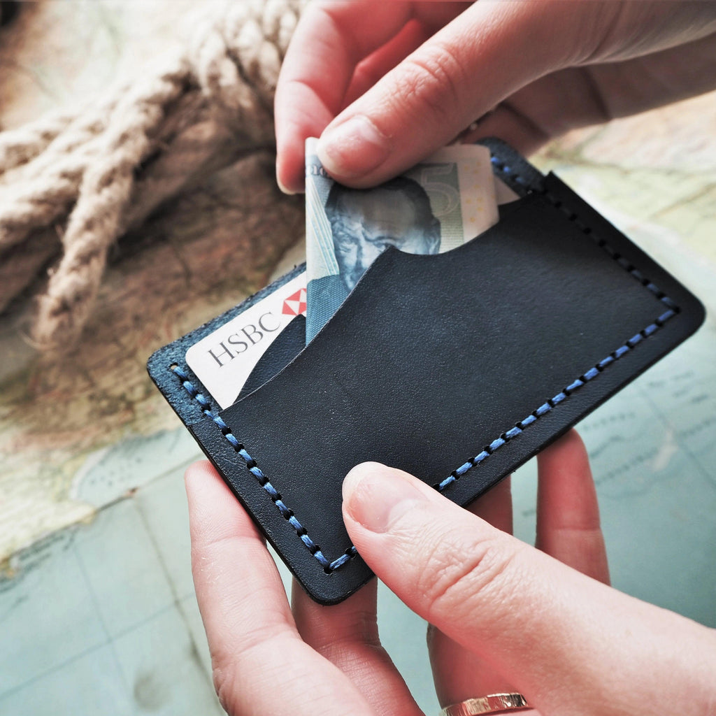 the wave cut credit card holder in use, with a five pound note being removed to pay for goods in a sailing shop