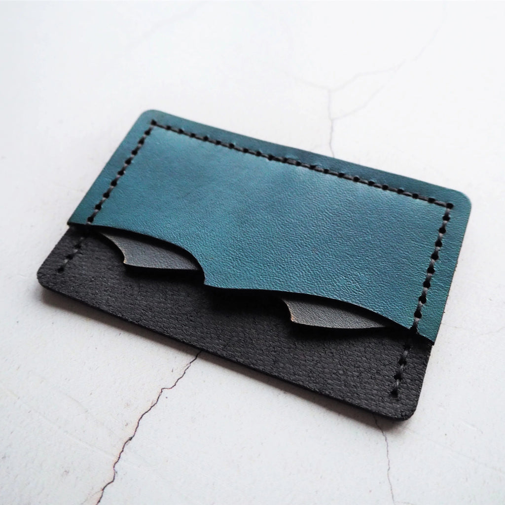 The front of the north sea wave card holder shows two compartments with the leather cut into the shape of waves, hand dyed in blue, grey and black and hand stitched with black thread