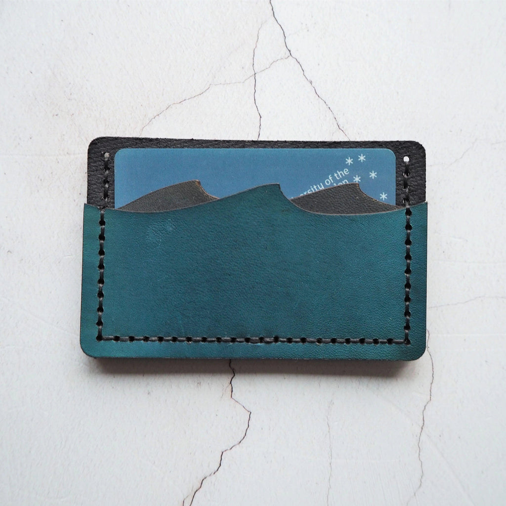 The front of the card holder shows the unique wave cut design of the card slots and demonstrates a card placed in one of the slots. Each slot can hold several cards as the leather will form to fit them