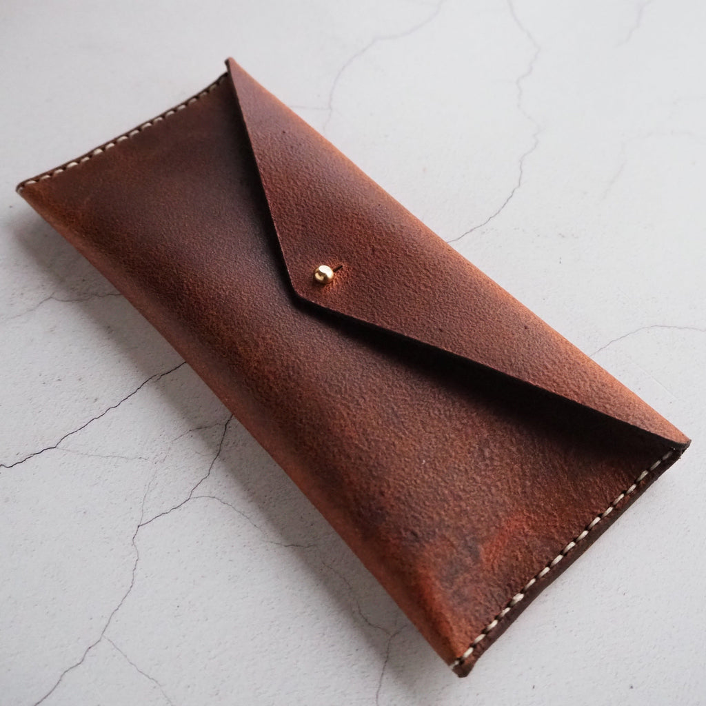 This rust coloured leather pencil case is hand stitched to last. The rugged leather has a vintage feel and is perfect for storing pens, pencils, glasses, make up and any other small trinkets.