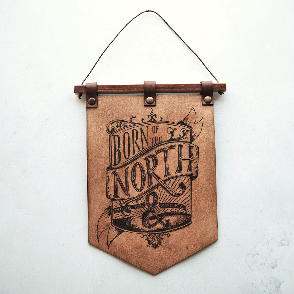 "born of the north banner made from hand dyed leather, a threaded wooden rail holds a leather banner which is engraved with an opulent crest style illustration containing the words ""Born of the North, amongst moorland and stone"" with moors in the background. The banner has a point to the bottom and is riveted to the wooden rail."