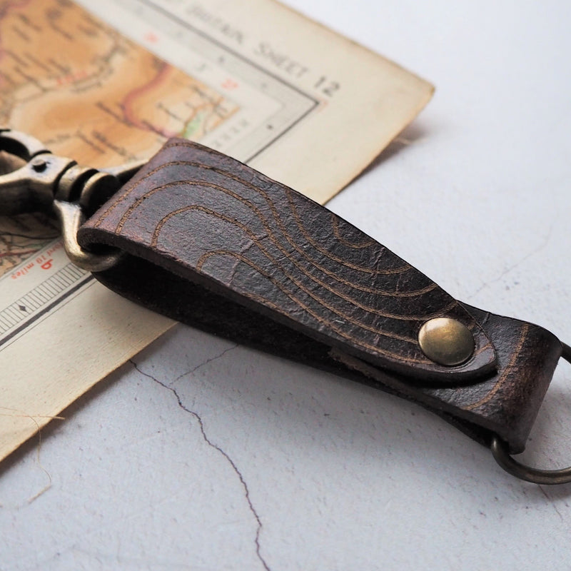 The Scafell Pike Leather Key Fob, Engraved with the contour lines of the Lake Districts and Englands tallest mountain, Scafell Pike. By Hord.