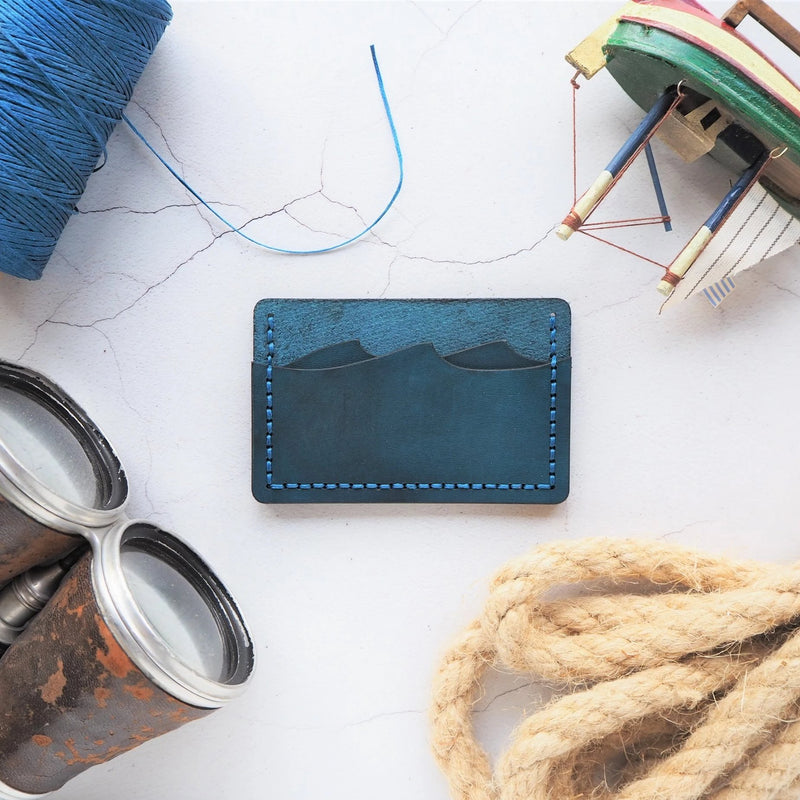 A credit card holder hand dyed and stitched in deep blue with a unique wave cut for the card slots