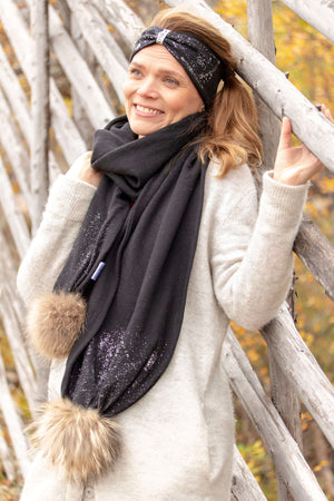 Super soft and warm black merino wool snow glow scarf with shiny details and wild fur pompoms made in Finland.