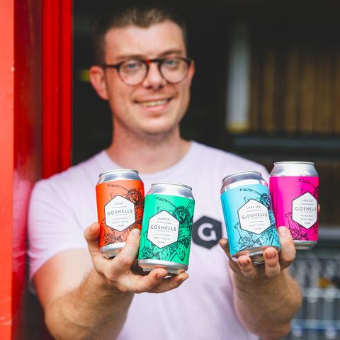 Tom Gosnell holding cans of our core range