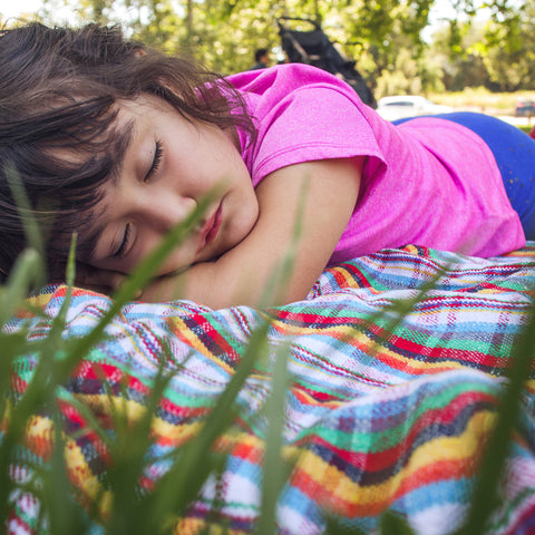child sleeping on Maria Canta plaid blanket